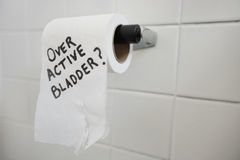 El primer del rollo del papel higiénico con el texto que pregunta por la vejiga publica foto de archivo libre de regalías