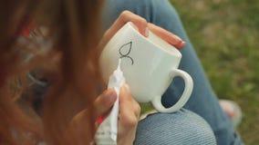El primer del ` s de la muchacha da el dibujo de un modelo en una taza blanca La muchacha pinta el ornamento que se sienta en la  almacen de metraje de vídeo