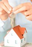 El primer del ` s de la mujer da llevar a cabo una casa modelo y una llave que sugieren la adquisición o el alquiler de la casa Foto de archivo
