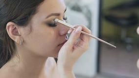 El primer del steadicam, la cara de una morenita joven hermosa con los ojos cerrados, maquillaje hace su maquillaje del ojo, dibu metrajes