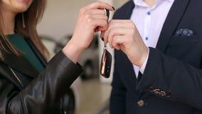 El primer del vendedor de coches da a muchacha las llaves al nuevo coche almacen de video