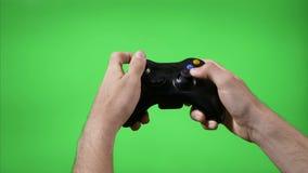 El primer del videojugador da jugar el videojuego que pulsa teclas del control remoto con el fondo de la llave de la croma - metrajes