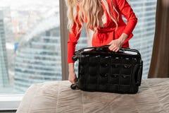 El primer desempaqueta la maleta que la empresaria rubia joven llega en una habitación con la maleta negra Mujer en coral rojo foto de archivo