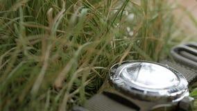 El primer en la hierba verde miente un reloj que se zambulle con énfasis en el movimiento de la mano de segundos roja en el negro almacen de metraje de vídeo