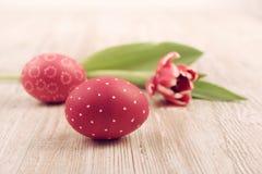El primer en rojo pintó el huevo de Pascua con el tulipán en la madera Foto de archivo libre de regalías
