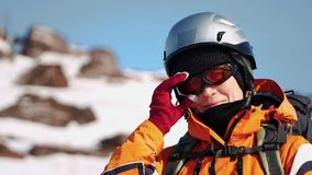 El primer, escalador se coloca en una montaña en un casco y una chaqueta caliente y fijar para arriba sus vidrios da almacen de video