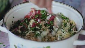 El primer extremo, hombres de las manos cucharea para revolver los ingredientes para cocinar la ensalada en un pote metrajes