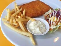 El primer frió pescados, microprocesadores y la ensalada en un plato blanco en TA amarilla Fotos de archivo