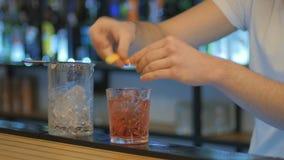 El primer - frotación del camarero el vidrio con la cáscara de naranja y adorna el cóctel con él almacen de metraje de vídeo