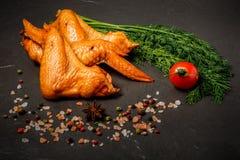El primer fum? las alas de pollo con eneldo, el tomate y las especias fotografía de archivo