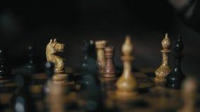 El primer, la mano del hombre indio con dudar largo de la pulsera hace vuelta a la reina en el tablero de ajedrez en el torneo de almacen de video