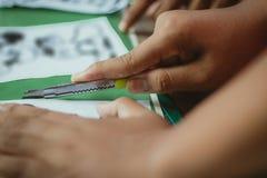 El primer a las manos de estudiantes está cortando impresiones y etiquetas engomadas Imágenes de archivo libres de regalías