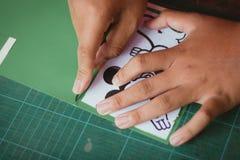 El primer a las manos de estudiantes está cortando impresiones y etiquetas engomadas Foto de archivo