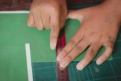 El primer a las manos de estudiantes está cortando impresiones y etiquetas engomadas Fotos de archivo