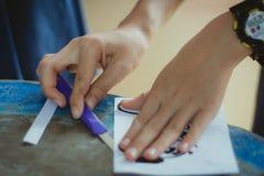 El primer a las manos de estudiantes está cortando impresiones y etiquetas engomadas Foto de archivo libre de regalías