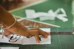 El primer a las manos de estudiantes está cortando impresiones y etiquetas engomadas Imagen de archivo libre de regalías