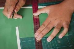 El primer a las manos de estudiantes está cortando impresiones y etiquetas engomadas Imagenes de archivo