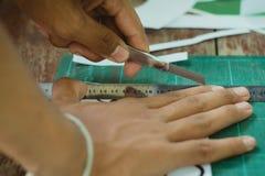 El primer a las manos de estudiantes está cortando impresiones y etiquetas engomadas Fotografía de archivo libre de regalías