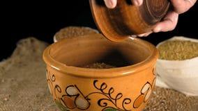 El primer, las manos de una mujer mayor vierte fuera de una placa de madera en Clay Pot Of Wheat Grains almacen de video