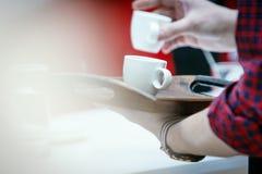 El primer, las tazas de café blancas holded por las manos del barista Imagen de archivo