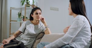 El primer maduro de dos hermanas charla junto en el sofá que tienen una conversación concentrada en una sala de estar espaciosa almacen de metraje de vídeo
