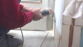El primer, manos de un carpintero está perforando una pared metrajes