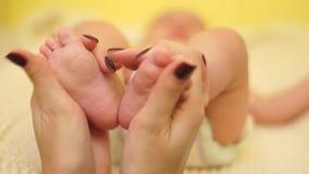 El primer, mi madre lleva a cabo suavemente pies del bebé en sus manos almacen de metraje de vídeo