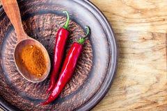 El primer molió escamas de las pimientas de chile y el polvo de chile en la placa oscura, chile picante maduro rojo fresco en vie Imágenes de archivo libres de regalías