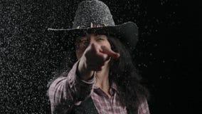 El primer, mujer hermosa en un sombrero de vaquero regado con nieve tira una pistola improvisada y sonrisas metrajes