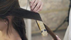 El primer, peluquero hace un corte de pelo a una muchacha con el pelo oscuro largo, enrolla un filamento del pelo, pinzas de las  metrajes