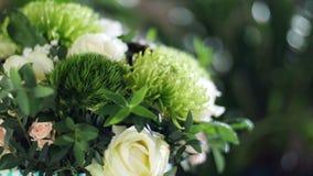 El primer, ramo de la flor en los rayos de la luz, rotación, la composición floral consiste en el verde de Brunia, Rose de almacen de metraje de vídeo
