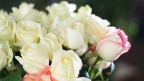 El primer, ramo de la flor en los rayos de la luz, rotación, la composición floral consiste las rosas blancas En el fondo almacen de metraje de vídeo