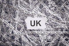 El primer rasgado junta las piezas y las cintas del papel con la palabra Reino Unido Foto de archivo