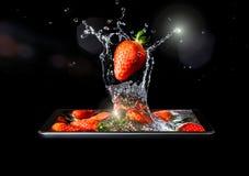 El primer rojo maduro de la fresa adentro salpica del agua y de la luz del sol que caen en el agua en un smartphone aislada en un Imagen de archivo
