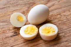 El primer sin pelar hirvió el huevo y los medios huevos en el fondo blanco, Imagenes de archivo