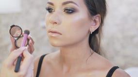 El primer, steadicam, artista de maquillaje pone un highlighter en los pómulos, nariz, labio superior del cliente, hace almacen de video