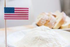 El primer tiró de bandera americana y de la harina en una placa Rebanadas de pan en el fondo Fotos de archivo libres de regalías