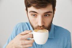 El primer tiró de capuchino que sorbía del individuo barbudo lindo del inconformista mientras que trabajaba en café como freelanc fotografía de archivo libre de regalías
