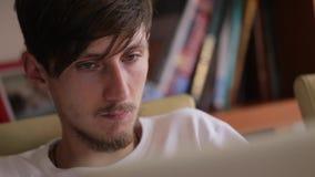 El primer tiró de Internet que practicaba surf del hombre joven, adolescente que usaba la PC de la tableta Lectura de la persona, metrajes