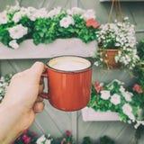 El primer tiró de la mano de la mujer con la taza de café del vintage contra las plantas en conserva y las flores Imagen de archivo