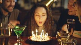 El primer tiró de la mujer bonita joven que soplaba hacia fuera velas en la torta de cumpleaños La gente feliz es de risa y que a metrajes