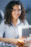 El primer tiró de la mujer feliz que hacía puntadas planas en la máquina de coser Imagenes de archivo