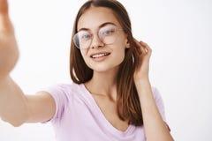 El primer tiró de la mujer joven sensual y femenina apuesta confiada que chasqueaba el pelo detrás de la sonrisa coqueta del oído fotos de archivo