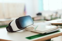 El primer tiró de las auriculares de la realidad virtual en la tabla con el libro de texto y el lápiz imágenes de archivo libres de regalías