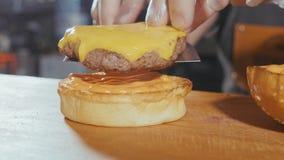 El primer tiró de las manos del ` s del cocinero que preparaban una hamburguesa con la croqueta y el queso de la carne de vaca Fotografía de archivo