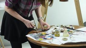 El primer tiró de las manos femeninas que exprimían hacia fuera un tubo de la pintura sobre la paleta almacen de video