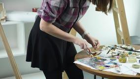 El primer tiró de las manos femeninas que exprimían hacia fuera un tubo de la pintura sobre la paleta metrajes