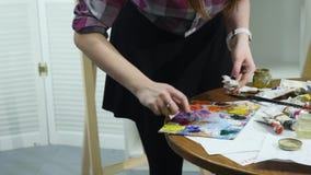 El primer tiró de las manos femeninas que exprimían hacia fuera un tubo de la pintura sobre la paleta almacen de metraje de vídeo