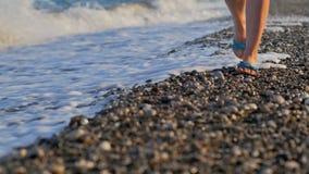 El primer tiró de las piernas delgadas del ` s de la mujer que caminaban en una costa del guijarro en la puesta del sol metrajes
