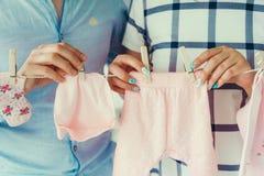 El primer tiró de los padres del futuro que colgaban la ropa rosada para su niño recién nacido en la cuerda para tender la ropa u Foto de archivo libre de regalías